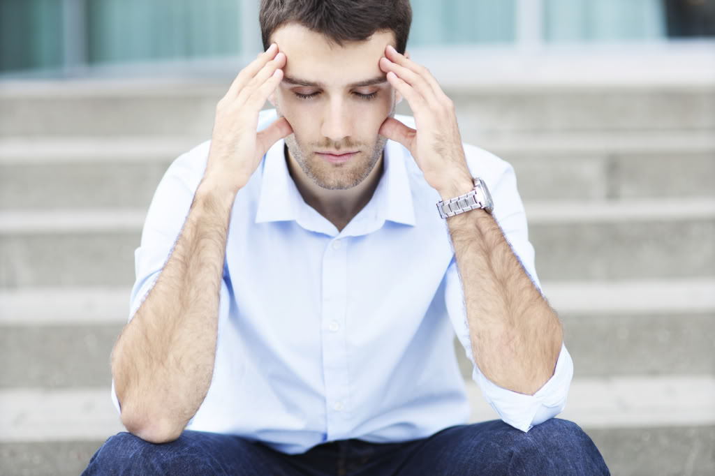 Man sitting on steps, holding head because he has a headache caused by TMJ disorder
